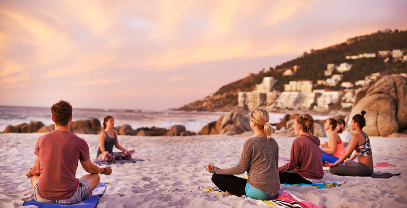 group of people on a beach yoga retreat