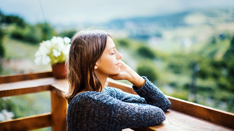 Young woman on a wellness retreat enjoying a fresh air on the mountain during summer morning