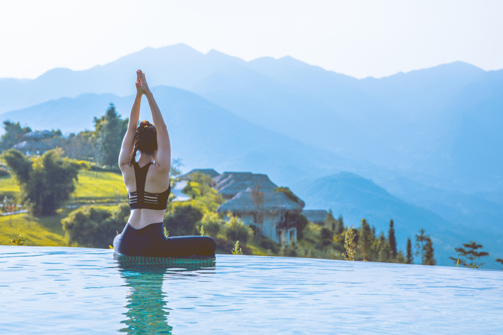 woman practicing yoga on pool above the Mountain peak