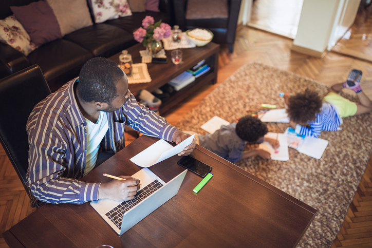 father working from home while keeping an eye on the kids