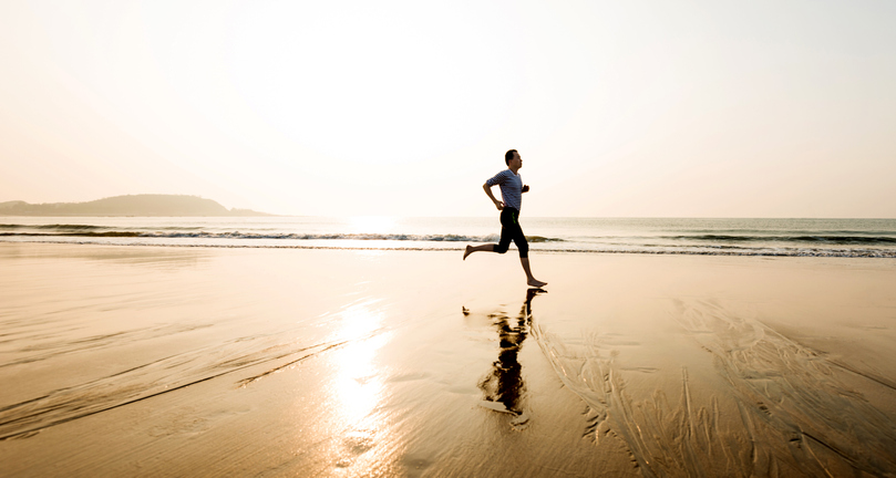 man running by himself on the beach