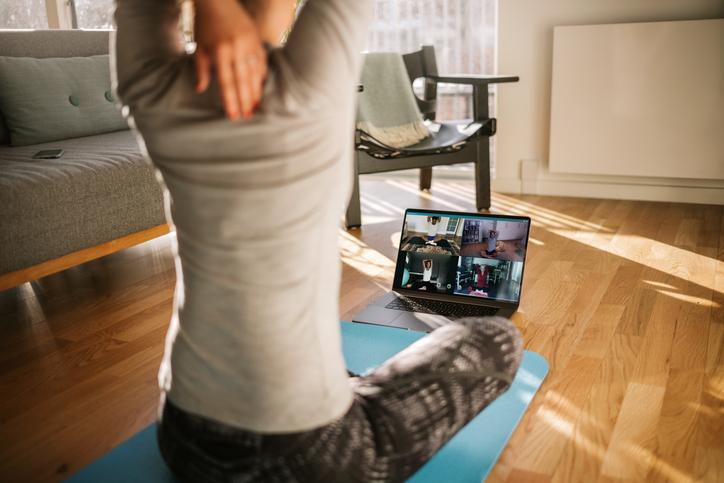 woman doing virtual yoga at home